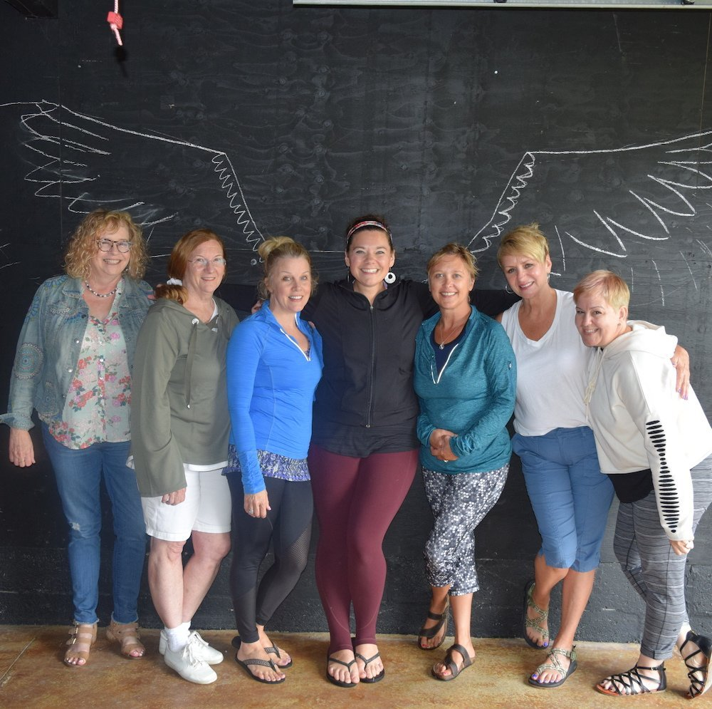 Lindsay Madison posing with a group of women while in front of a chalk drawing of wings