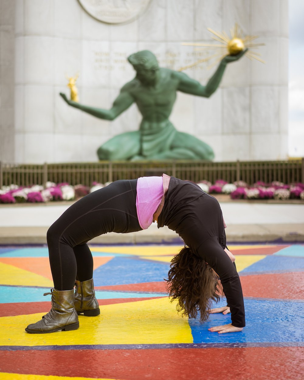 Lindsay Madison in a back bend in front of the spirit of detroit statue