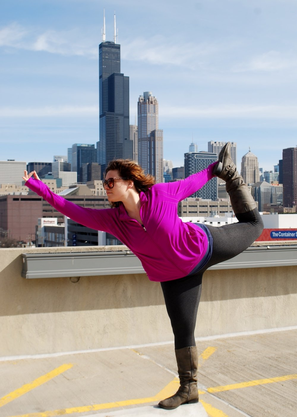 Lindsay Madison in a yoga post standing on top of a parking garage over looking a city